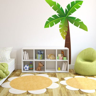 Jungle tree wall sticker, jungle wall stickers. Image shows tall palm tree stickers with brown trunk and green and yellow toned leaves. Sticker has been placed in a playroom behind a small storage unit and a green chair.