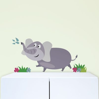 Elephant wall sticker, jungle wall stickers. This sticker design shows a grey elephant squirting water from its trunk with grass and flowers at it's feet. This sticker has been placed above a white set of drawers.