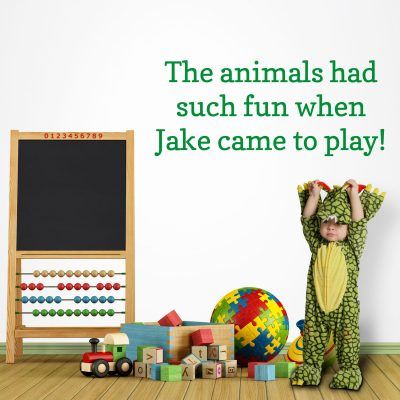 """Personalised jungle quote wall sticker, jungle wall stickers. This sticker is in green text saying """"The animals had such fun when Jake came to play!"""" The sticker has been placed in a playroom scene next to a small blackboard and above a child in a dinosaur costume."""