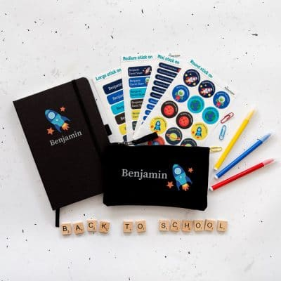 Space Back to school Mega Bundle. Featuring a black notebook with the name Benjamin in grey with a blue spaceship below. A black pencil casewith the name and the spaceship to the right. And four sheets of stick on name labels.
