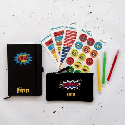Comic book back to school mega bundle. Includes four sheets of stick on name labels. Black notebook with the name Finn in yellow on bottom of notebook and yellow and blue star explosion with the word BAM! in red. Black Pencil case with name in yellow and the word POOOW!! in a blue and white star explosion.