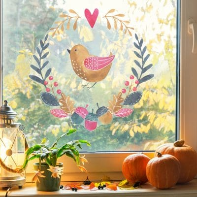 multicoloured woodland window sticker (Option 1), autumn window stickers. Gold bird in middle of a wreath made of blue, green and pink leaves and acorns with pink heart at the top.