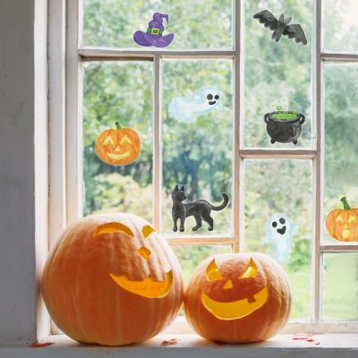 cute halloween window stickers, halloween window stickers, image shows stickers pasted on a window with two pumpkins in front