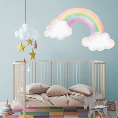 pastel rainbow with clouds wall sticker above a cot on a blue grey wall