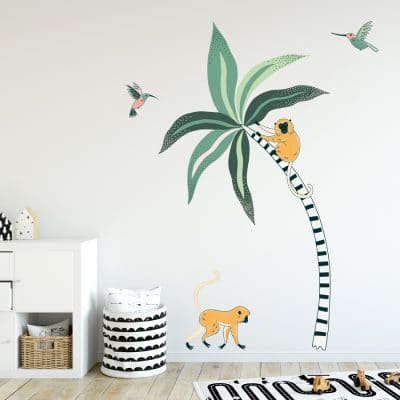 Tropical Palm And Monkeys Wall Stickers. Image displays a room with a large stripy palm tree sticker with green leaves, a yellow monkey on the tree and one walking along the ground, and two pink and green humming birds on the wall.
