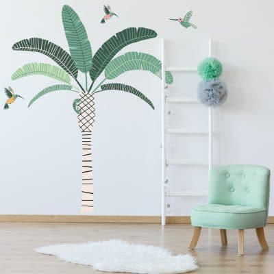 Tropical Palm Tree Wall Sticker Jungle wall sticker. Image showing a room with a green chair and a white rug and a stripy palm tree with green leaves and green and pink hummingbirds stickers on the wall.