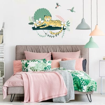 Cheetah and hummingbirds wall sticker pack, jungle wall stickers, safari wall stickers. Featuring a cheetah relaxing on a branch with flowers and green plants around. There is also to pink and green coloured humming birds. Jungle wall sticker, is displayed above a pink bed setting.