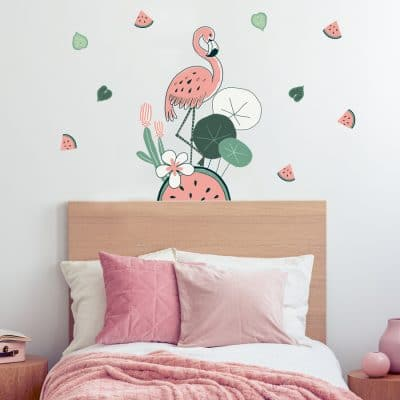 Flamingo and Watermelon jungle wall stickers. Features a pink flamingo standing on a large watermelon with a cactus and other plants around. Smaller pink and green watermelon slice stickers are positioned around. Stickers are placed above a pink bedspread.