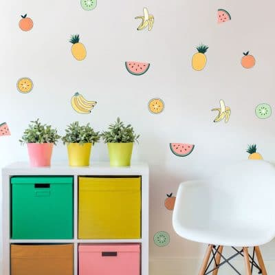 Tropical Fruit wall stickers, jungle wall stickers. Image features tropical fruit stickers on wall around a small white chair and a white set of drawers with colourful potted plants on top.
