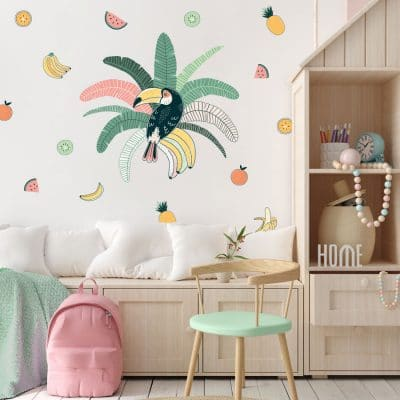 Tropical toucan wall sticker pack, jungle wall sticker. Sticker is of a toucan sat in the centre of green and pink palm leaves. Surrounding the main sticker is colourful fruit, pineapples/bananas/melon/oranges. Sticker has been placed in a bedroom above a low wooden unit and next to tall shelves.