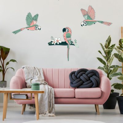 Tropical parrot wall sticker pack, jungle wall stickers. Image shows three pink and mint green parrot stickers, two are flying and one is sat on a dark green branch with a white flower. The stickers have been placed on a white wall above a pinka sofa with green, grey and natural toned furnishings.