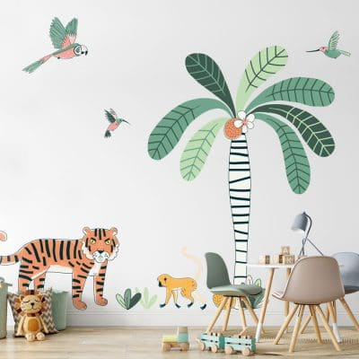 jungle wall sticker pack, jungle wall stickers. Image shows a large striped tree trunk with bright green leaves and coconuts, a tiger, monkey, a parrot and two smaller birds. The sticker has been placed on a light plain wall behind a set of small table and chairs.