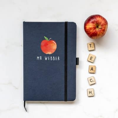 Personalised apple notebook in blue features a rainbow design with personalised name underneath and is a perfect gift for a teacher or teaching assistant to say thank you