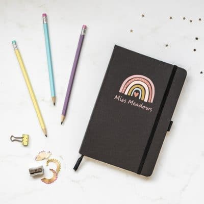 Personalised rainbow heart notebook in black features a rainbow design with personalised name underneath and is a perfect gift for a teacher or teaching assistant to say thank you