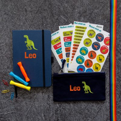 Mega back to school bundle. Black pencil case, blue notebook and four sheets of name labels featuring the name Jasper in orange with a green dinosaur to the right.