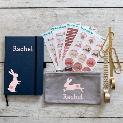 bunnies back to school mini bundle. Blue notebook with pink rabbit on bottom left with name in large pink text middle top. Grey pencil case with leaping pink rabbit in centre with name text in pink below. 4 sheets of stick on name labels.