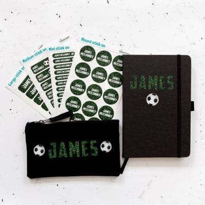 Mega back to school bundle. Black pencil case, black notebook and four sheets of name labels featuring the name James in a grass print with footballs.