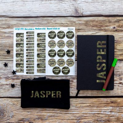 Mega back to school bundle. Black pencil case, blue notebook and four sheets of name labels featuring the name Jasper in a camouflage print.