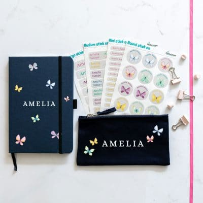 Butterflies back to school mega bundle. Featuriong four sheets of stick on name labels, a blue note book and black pencil case. Pencil case and notebook have write writing for the name and it is surrounded in pastel butterflies.