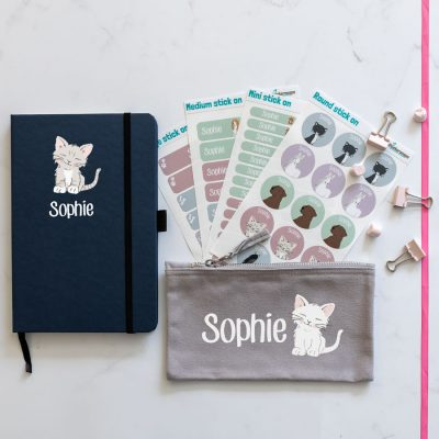 cat back to school mega bundles. blue notebook with cat illustration in centre with name text in white underneath. grey pencil case with image of cat in centre with name text in white to the left. 4 sheets of stick on name labels.