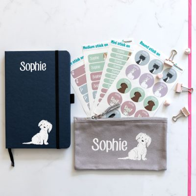 dog back to school mini bundle. black notebook with dog illustration bottom right with name text in white at top centre. grey pencil case with image of dog on right with name text in white to the left. 4 sheets of stick on name labels.