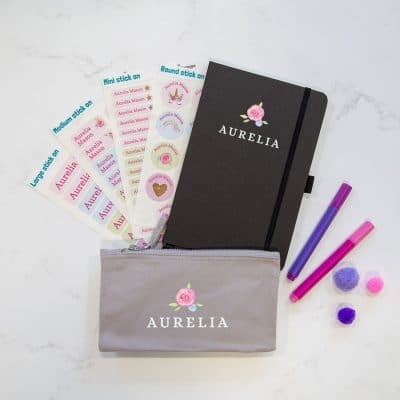 Ditsy rose back to school mega bundle. Featuring a black notebook and grey pencil case, both with white text for the name and a pink rose above. There is also four sheets of stick on name labels.
