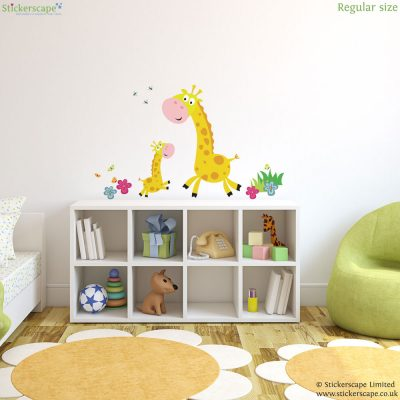 Giraffe family wall sticker pack, jungle wall stickers. Sticker is shown with small giraffe and large giraffe facing each other in the centre with flowers, bumblebees and butterflies around them. This sticker has been placed in a childs bedroom above a short white unit next to a bed and green chair.