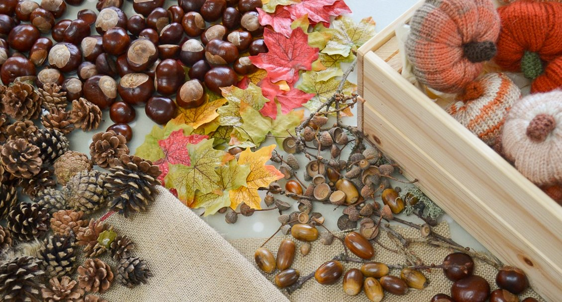 Decorating an Autumn wreath for October using pine cones, conkers and leaves
